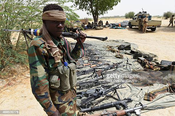 A Chadian soldier stand guard next to captured arms on April 3 2015 in Malam Fatori in northeastern Nigeria which was retaken from Islamist Boko...
