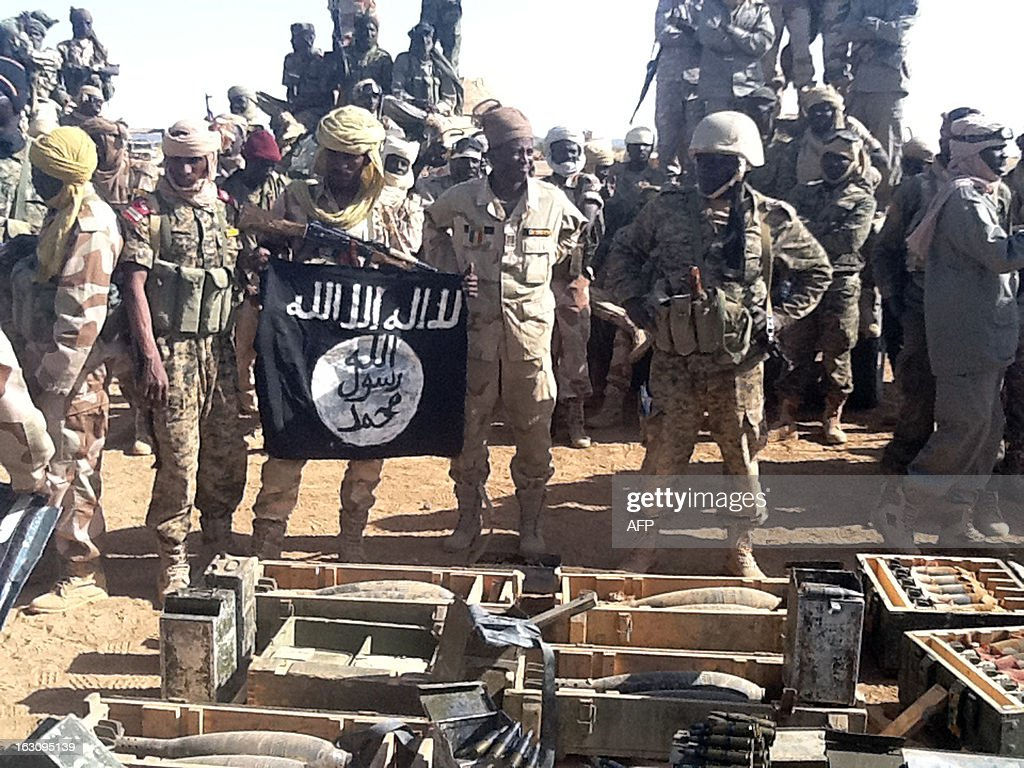 Chadian soldiers show a flag of Aqim and weapons recovered after violent clashes with Islamist militants on March 3, 2013 in Tessalit in the Ifoghas mountains, northern Mali. Chad says its troops in northern Mali have killed Mokhtar Belmokhtar, the one-eyed Islamist leader who masterminded an assault on an Algerian gas plant in January that left 37 foreign hostages dead. The announcement came amid continued fighting in the mountains of northern Mali, where France on Sunday said a third French soldier had been killed since it launched operations against Islamist rebels in mid-January.