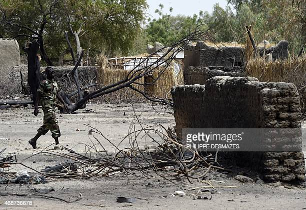 A Chadian soldiers walks past a burnt house on April 6 2015 in N'Gouboua near Lake Chad in Chad which was attacked by Islamist group Boko Haram on...