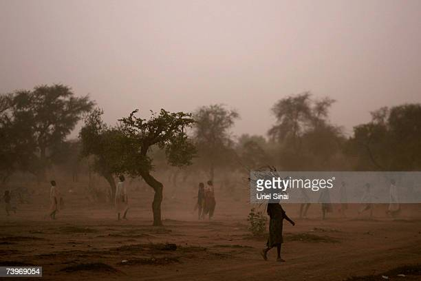 A Chadian woman collects fire wood as Chadian boys play football as the sun comes down over Habile IDP Camp near the border with Sudan April 20 2007...