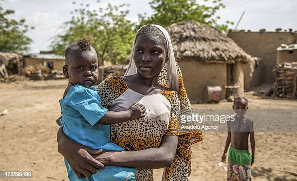 N'DJAMENA CHAD JUNE 22 A Chadian woman holding her kid is seen in a village near the capital N'djamena Chad on June 22 2015 Around %85 of the people...