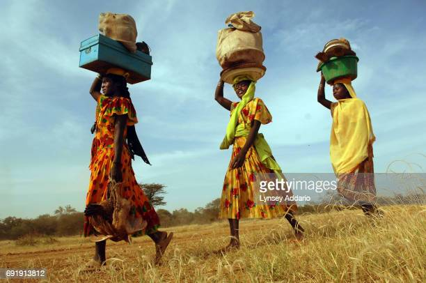 Chadian women from one of a string of roughly ten small villages walk towards Goz Amir with their belongings salvaged after their village had been...