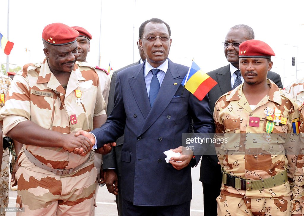 Chad's President Idriss Deby Itno (C) shakes hands with general of the Chadian contingent in Mali Oumar Bikimo (L) and second-in-command major and his son Mahamat Idriss Deby Itno (R) during a welcome ceremony, on May 13, 2013, in N'Djamena. Some 700 Chadian soldiers returned home to a heroes' welcome after a bloody campaign fighting Islamic insurgents in northern Mali. AFP PHOTO / STR