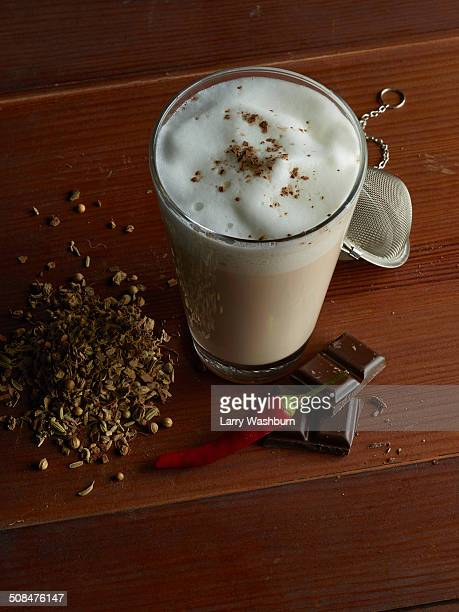 Chai latte surrounded by chocolate, chili, tea and spices