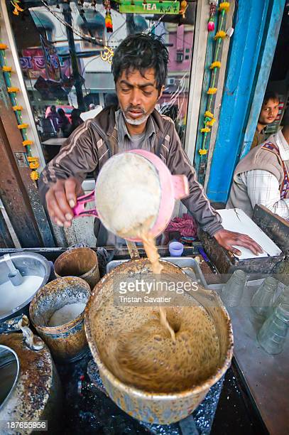 CONTENT] Chai wallah preparing a batch of chai at a street tea stall man worker street vendor pot boiling cooking milk tea sift stove street food