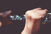 Hands with arthritis stretching a stainsless steel chain. Fighting the illness