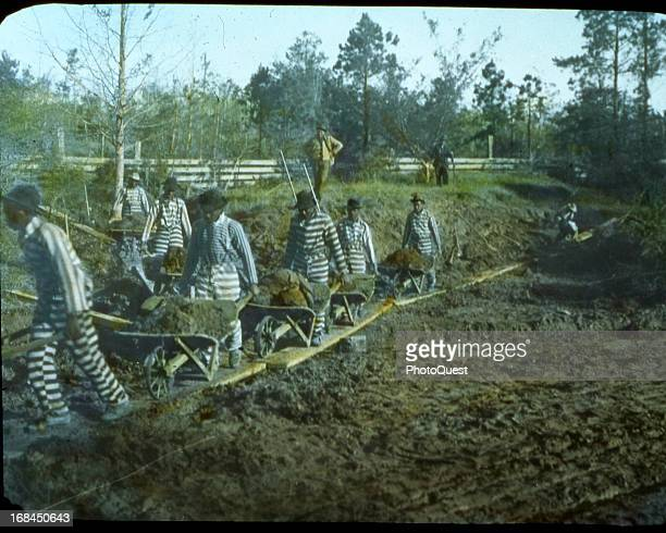 A chain gang of convicts working on improving a Louisiana road under guard Louisiana circa 1920s