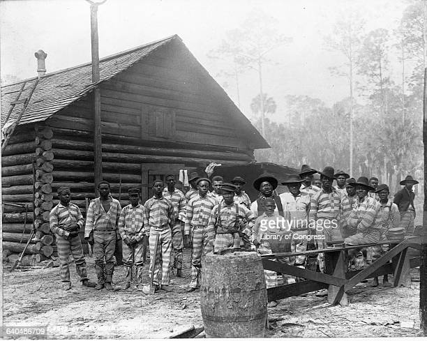 A chain gang stands outside a rustic log cabin 1898