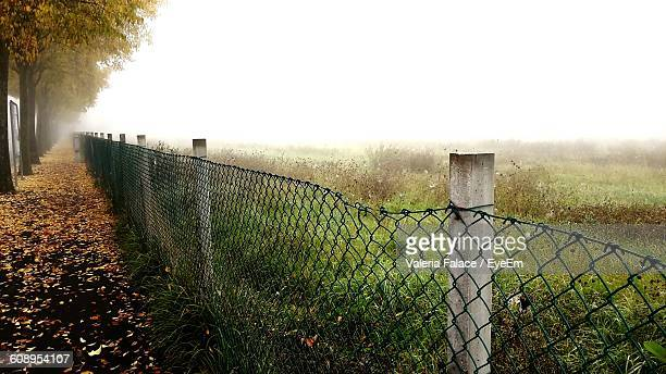 Chainlink Fence On Grassy Field Against Clear Sky