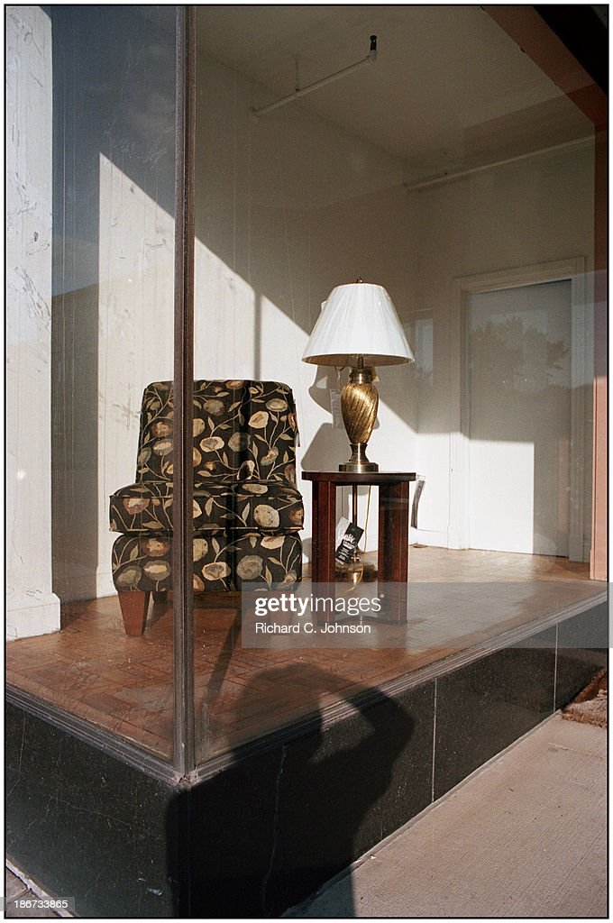 CONTENT] Chair and lamp, table in discount furniture storefront window