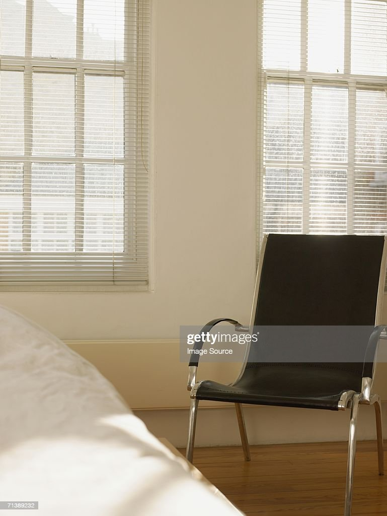 Chair beside a bed : Stock Photo
