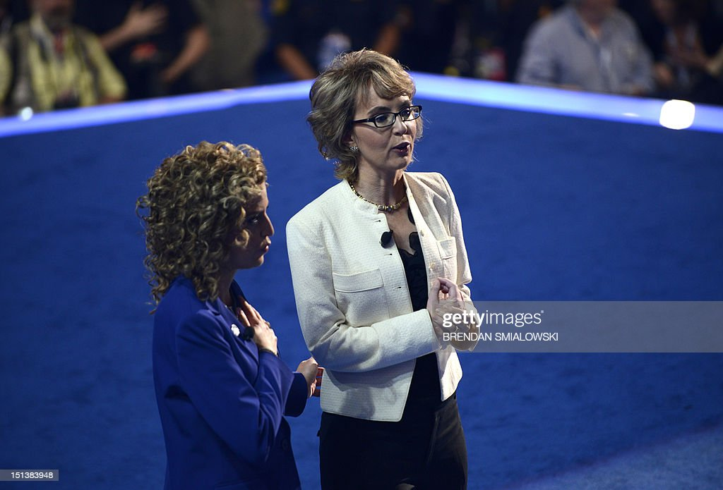 Chair of the Democratic National Committee Debbie Wasserman Schultz (L) and former congresswoman Gabrielle Giffords deliver the Pledge of Allegiance at the Time Warner Cable Arena in Charlotte, North Carolina, on September 6, 2012 on the final day of the Democratic National Convention (DNC). US President Barack Obama is expected to accept the nomination from the DNC to run for a second term as president. AFP PHOTO Brendan SMIALOWSKI
