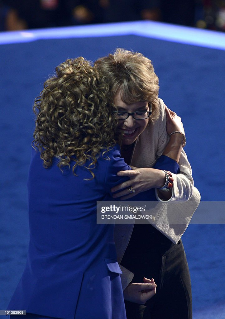 Chair of the Democratic National Committee Debbie Wasserman Schultz (L) and former congresswoman Gabrielle Giffords embrace after Giffords delivered the Pledge of Allegiance at the Time Warner Cable Arena in Charlotte, North Carolina, on September 6, 2012 on the final day of the Democratic National Convention (DNC). US President Barack Obama is expected to accept the nomination from the DNC to run for a second term as president. AFP PHOTO Brendan SMIALOWSKI