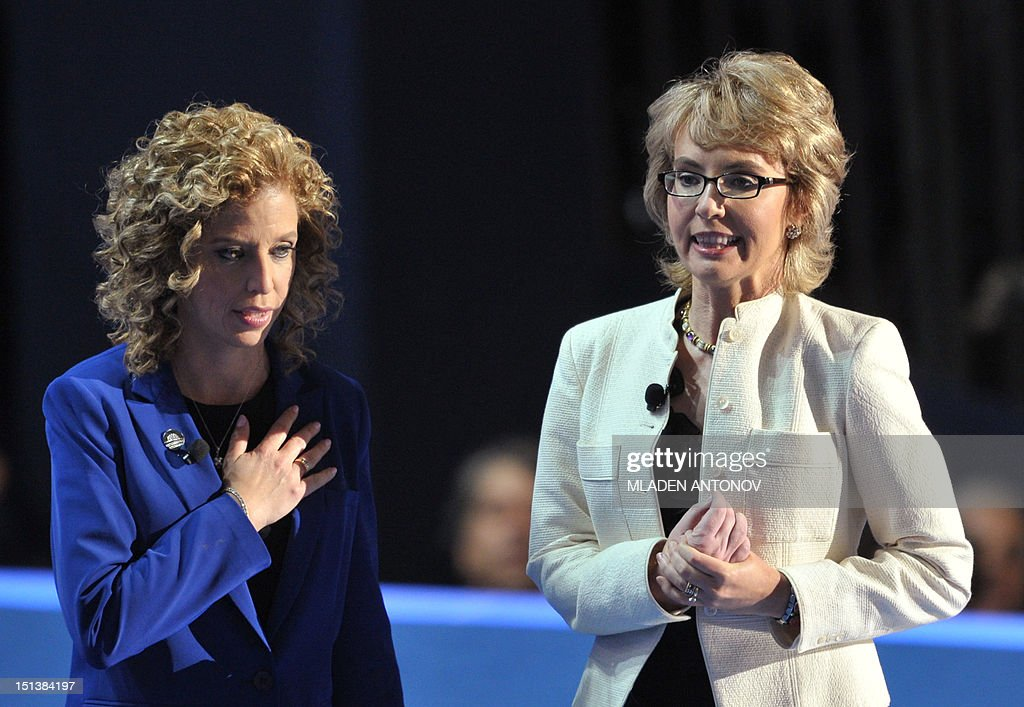 Chair of the Democratic National Committee Debbie Wasserman Schultz (L) and former congresswoman Gabrielle Giffords deliver the Pledge of Allegiance at the Time Warner Cable Arena in Charlotte, North Carolina, on September 6, 2012 on the final day of the Democratic National Convention (DNC). US President Barack Obama is expected to accept the nomination from the DNC to run for a second term as president. AFP PHOTO Mladen ANTONOV