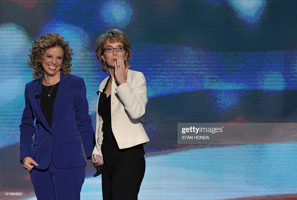Chair of the Democratic National Committee Debbie Wasserman Schultz (L) and former congresswoman Gabrielle Giffords acknowledge the audience at the Time Warner Cable Arena in Charlotte, North Carolina, on September 6, 2012 on the final day of the Democratic National Convention (DNC). US President Barack Obama is expected to accept the nomination from the DNC to run for a second term as president. AFP PHOTO Stan HONDA