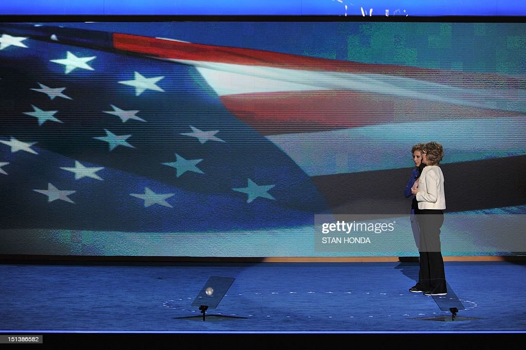 Chair of the Democratic National Committee Debbie Wasserman Schultz (L) stands with former congresswoman Gabrielle Giffords as she delivers the Pledge of Allegiance at the Time Warner Cable Arena in Charlotte, North Carolina, on September 6, 2012 on the final day of the Democratic National Convention (DNC). US President Barack Obama is expected to accept the nomination from the DNC to run for a second term as president. AFP PHOTO Stan HONDA