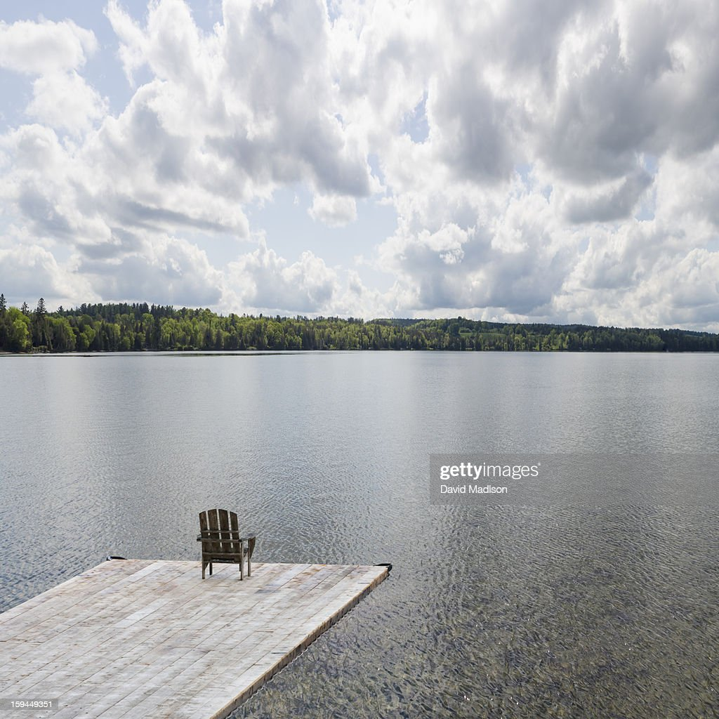 Chair on dock overlooking lake. : Stock Photo