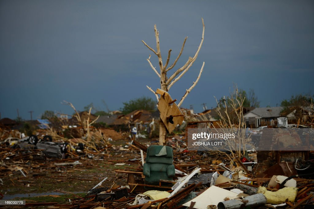 A chair sits against a bare tree next to a destroyed home on May 21, 2013 in Moore, Oklahoma. Families returned to a blasted moonscape that had been an American suburb Tuesday after a monstrous tornado tore through the outskirts of Oklahoma City, killing at least 24 people. Nine children were among the dead and entire neighborhoods vanished, with often the foundations being the only thing left of what used to be houses and cars tossed like toys and heaped in big piles. AFP PHOTO/Joshua LOTT