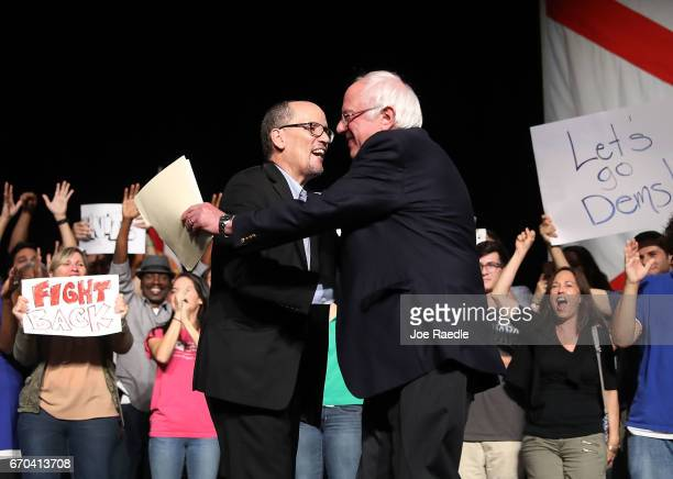 Chair Tom Perez hugs Sen Bernie Sanders as he introduces him to speak during their 'Come Together and Fight Back' tour at the James L Knight Center...