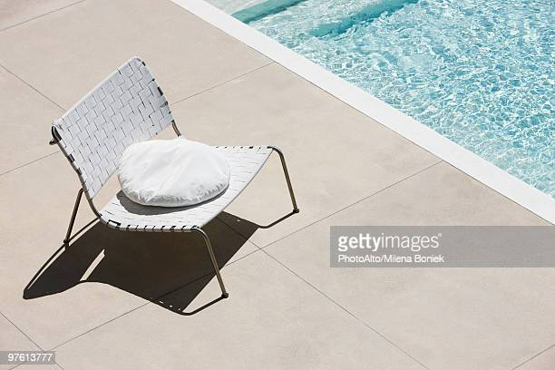 Chair with cushion at edge of pool