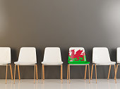 Chair with flag of wales in a row of white chairs. 3D illustration