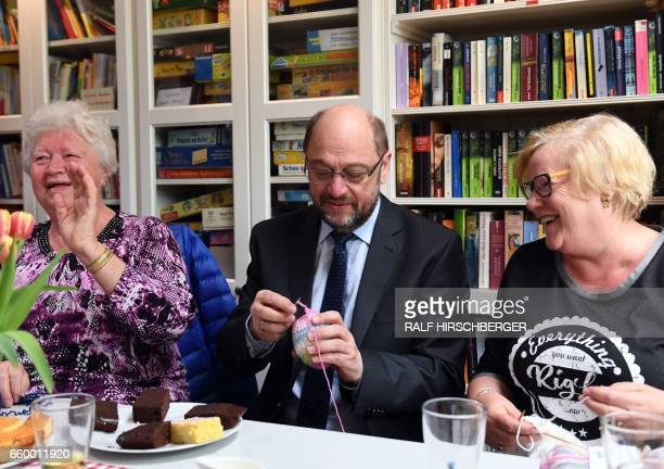 SPD chairman and candidate for Chancellery Martin Schulz knits during a visit to a mixed generation housing project on March 29 2017 in Teltow near...