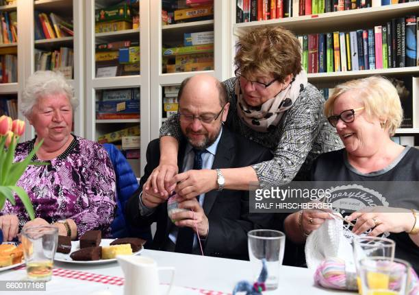 SPD chairman and candidate for Chancellery Martin Schulz learns how to crochet during a visit to a mixed generation housing project on March 29 2017...