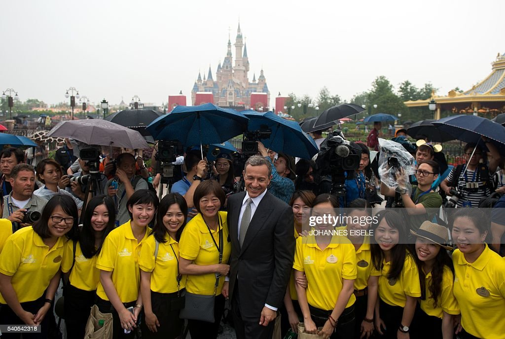 Chairman and CEO of Walt Disney Bob Iger poses with volunteers in front of the Enchanted Storybook Castle during the opening ceremony of the Shanghai...