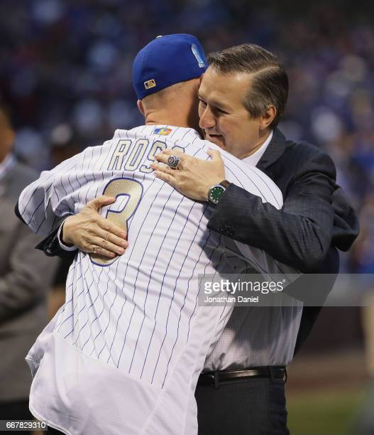 Chairman and owner Tom Ricketts of the Chicago Cubs hugs former player David Ross during a World Series Championship ring ceremony before a game...
