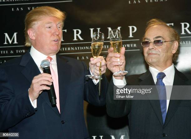Chairman and President of the Trump Organization Donald Trump and his partner developer Phil Ruffin share a champagne toast during an opening...