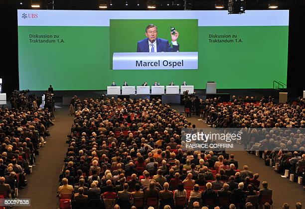 UBS Chairman Marcel Ospel is seen on a giant screen as he holds a voting device during an extraordinary shareholder meeting on February 27 2008 in...