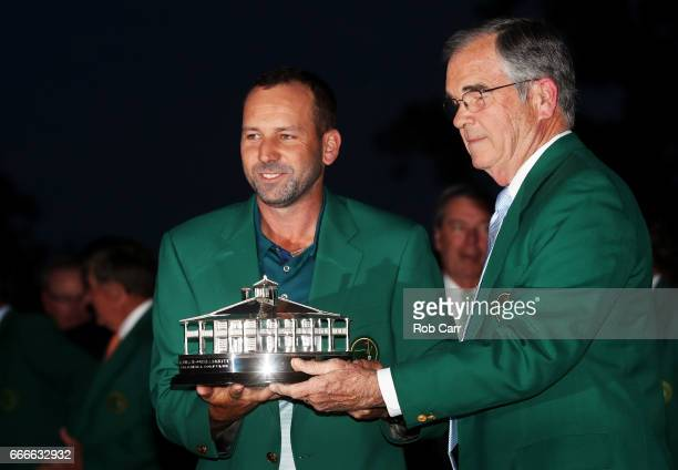 Chairman of Augusta National Golf Club William Porter Payne hands the Masters Trophy to Sergio Garcia of Spain during the Green Jacket ceremony after...