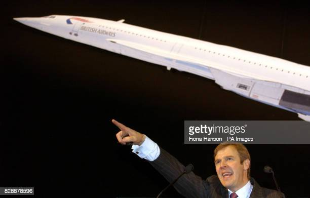 Chairman of Bonhams Robert Brooks points to a bidder hoping to grab one of the many Concorde momentos going under the hammer today at the British...