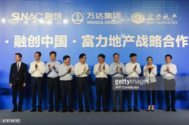 Chairman of China's Wanda Group Wang Jianlin chairman of Sunac China Holdings Limited Sun Hongbin and chairman of RF Properties Li Szelim applaud as...