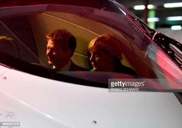 Chairman of German railway operator Deutsche Bahn Richard Lutz and German Chancellor Angela Merkel sit inside the cockpit of a special ICE high speed...