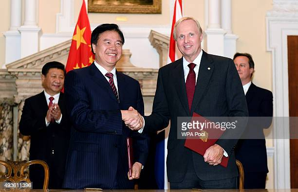 Chairman of oil and gas company Petro China Wang Yilin shakes hands with the Chief Executive of oil and gas company BP Bob Dudley during a commercial...