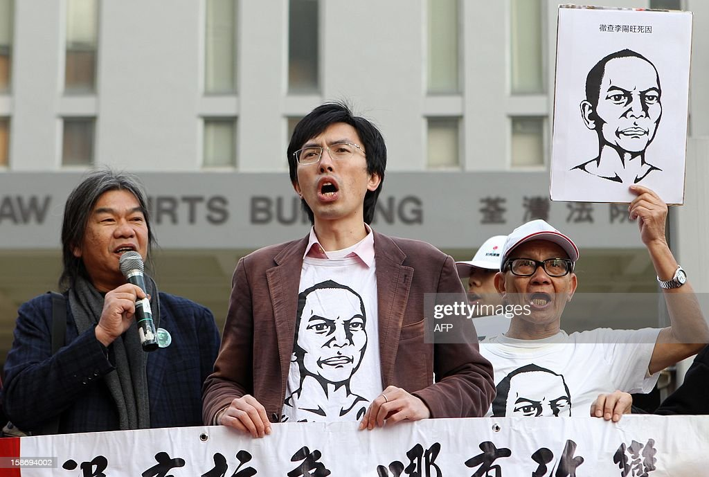 Chairman of pro-democracy party, League of Social Democrats, Leung Kwok-hung, also known as Long Hair (L), vice chairman Avery Ng (C) and a supporter holding a poster of Chinese dissident Li Wangyang protest before Ng's court appearance in Hong Kong on December 24, 2012. A Hong Kong pro-democracy activist was charged with 'nuisance' in court on December 24 after he allegedly threw a t-shirt at Chinese President Hu Jintao's motorcade in protest earlier this year. AFP PHOTO / Dale de la Rey