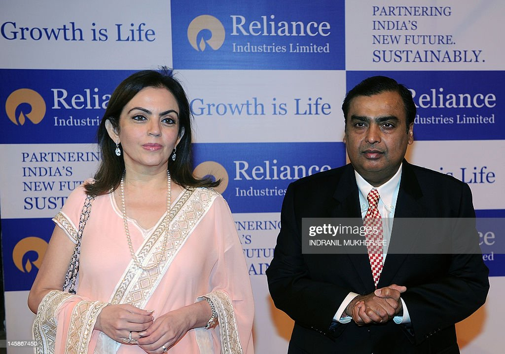 Chairman of Reliance Industries Limited Mukesh Ambani (R) arrives for the company's annual general meeting with his wife Nita in Mumbai, on June 7, 2012. Controlled by the elder of the two Ambani brothers, shares of Reliance Industries are held by one out of every four Indian investors. AFP PHOTO/ Indranil MUKHERJEE