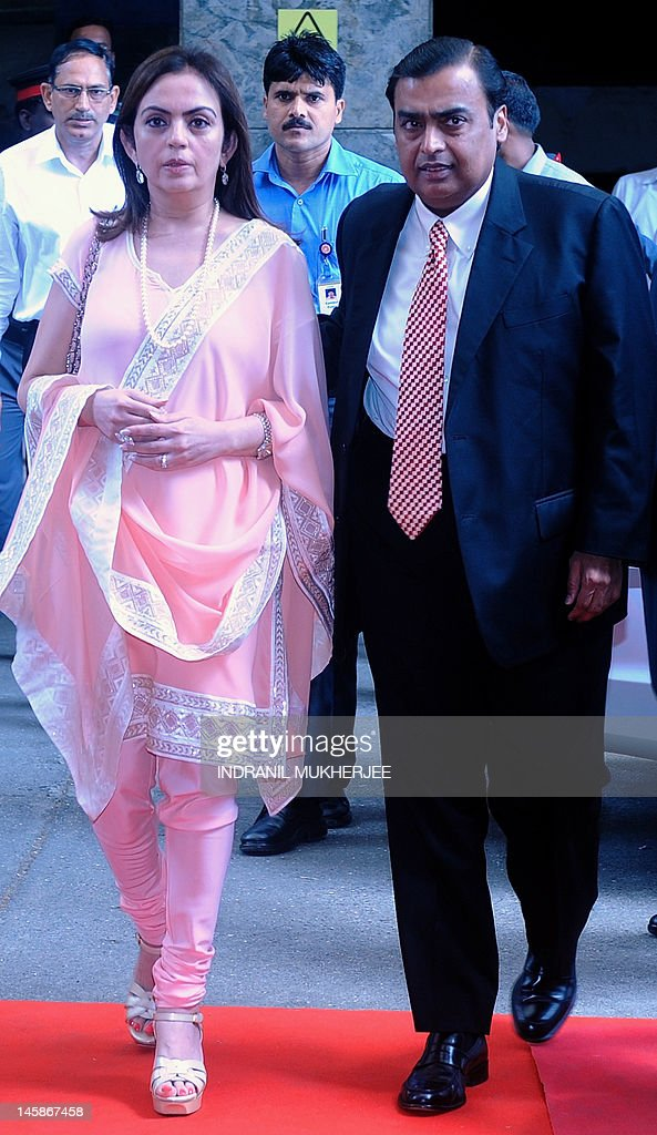 Chairman of Reliance Industries Limited Mukesh Ambani arrives for the company's annual general meeting with his wife Nita in Mumbai, on June 7, 2012. Controlled by the elder of the two Ambani brothers, shares of Reliance Industries are held by one out of every four Indian investors. AFP PHOTO/ Indranil MUKHERJEE
