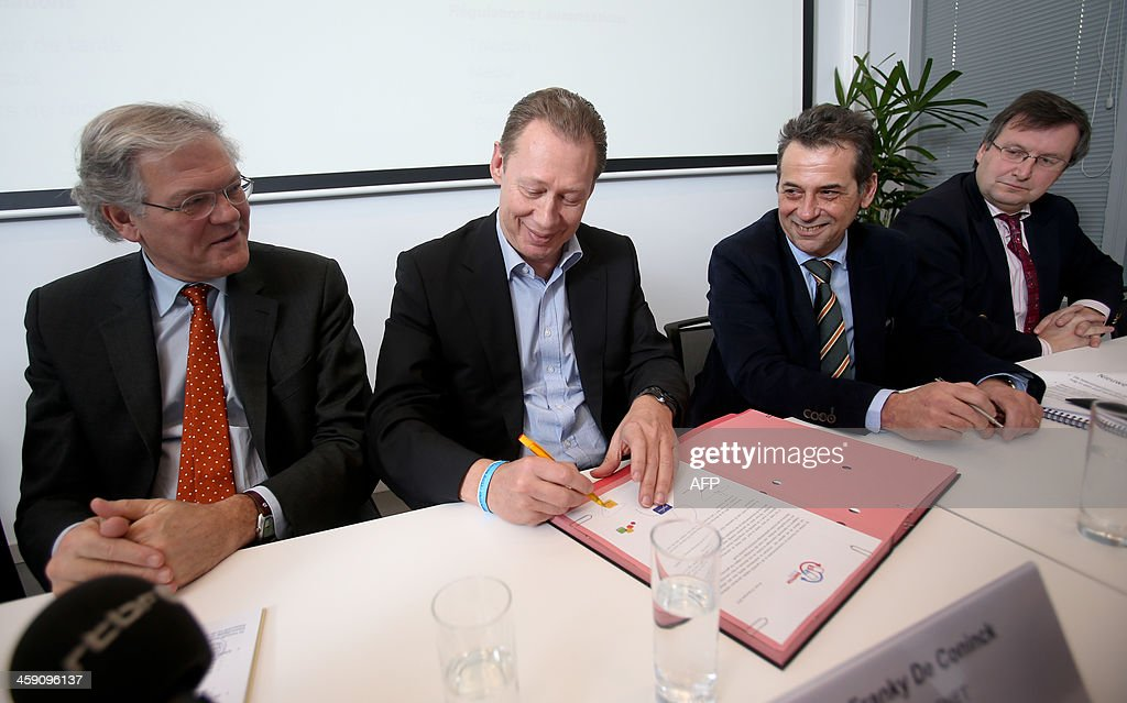 Chairman of the board of directors of state-owned Belgian telecom giant Belgacom Stefaan De Clerck, Telenet's Vice President for Public Affairs Franky De Coninck, Base's head of Corporate Affairs Edward Claessens and Mobistar's Secretary General Paul-Marie Dessart sign an agreement between the four big Belgian telecommunication groups and the Belgian Minister of Economy and Consumer Affairs on December 23, 2013 in Brussels.