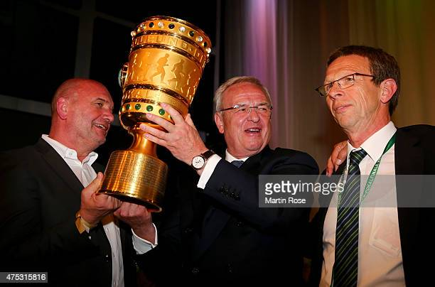 Chairman of the board of directors of Volkswagen Martin Winterkorn lifts the trophy next to Klaus Mohrs mayor of the city Wolfsburg during the VfL...
