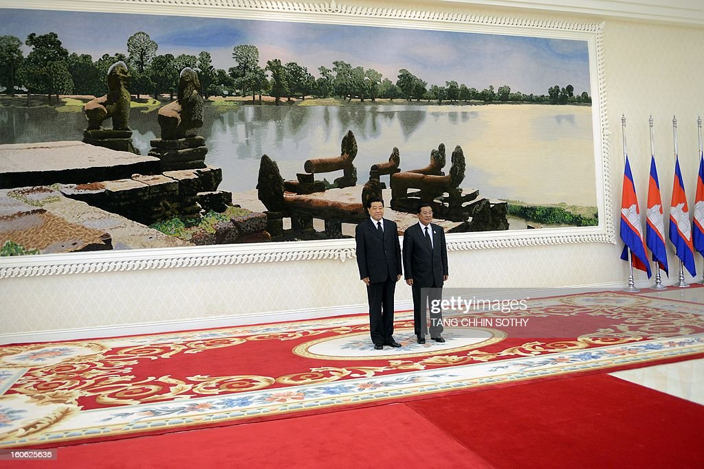 Chairman of the Chinese People's Political Consoltative Conference (CPPCC) Jia Qinglin (L) stands with Cambodian Prime Minister Hun Sen (R) during their meeting at the Peace Palace in Phnom Penh on February 4, 2013. Jia arrived here to pay his respects and attend the funeral of the late former king Norodom Sihanouk ahead of his cremation on February 4. AFP PHOTO / TANG CHHIN SOTHY