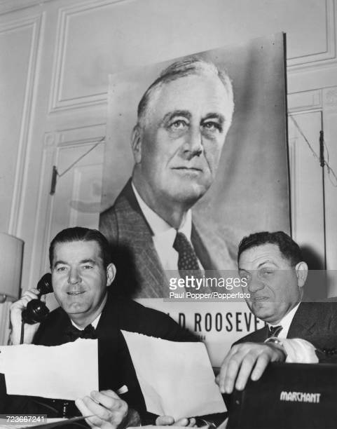 Chairman of the Democratic National Committee Robert E Hannegan pictured on left receiving a results sheet from a tribulator as he calls President...