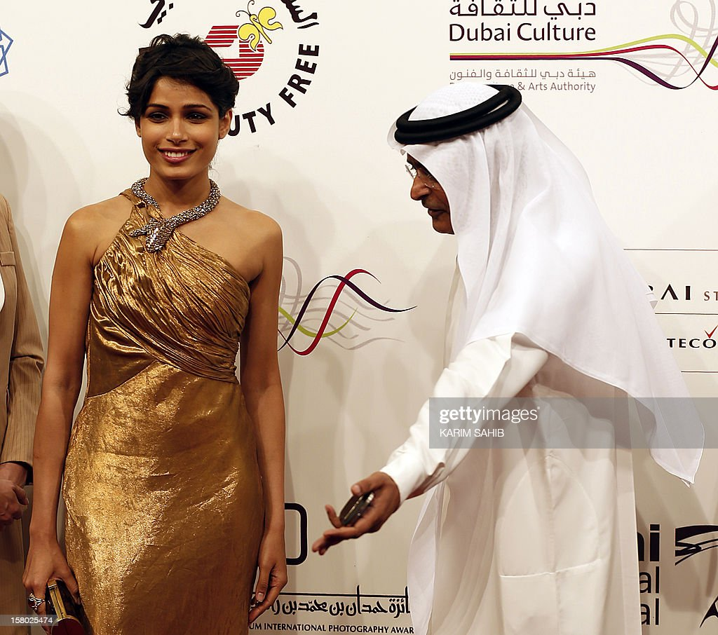 Chairman of the Dubai International Film Festival Abdulhamid Juma (R) gestures towards Indian actress Freida Pinto (L) as they pose for a photo during the opening ceremony of the festival in the Gulf emirate of Dubai on December 9, 2012. AFP PHOTO/KARIM SAHIB