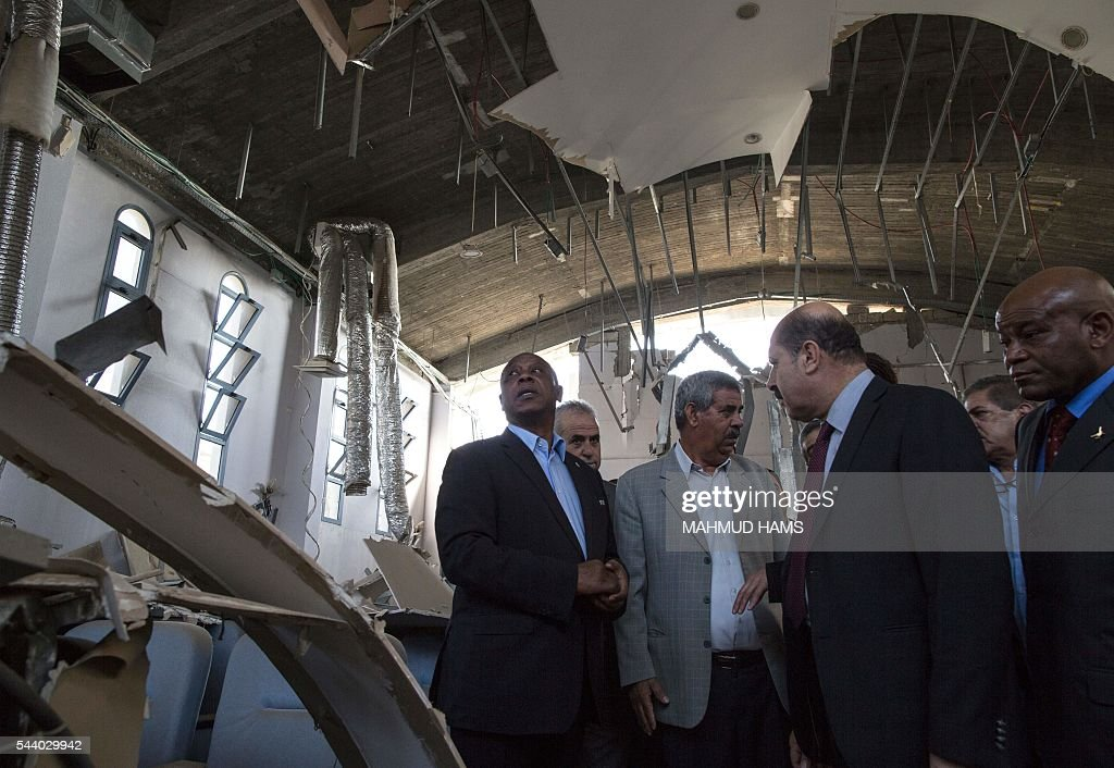 Chairman of the FIFA monitoring committee for Israel and Palestine, Tokyo Sexwale (L), visits the Palestinian Football Association (PFA) headquarters building that was destroyed during the 50-day war between Israel and Hamas-militants in the summer of 2014, in Beit Lahia in the northern Gaza Strip, on July 1, 2016. / AFP / MAHMUD