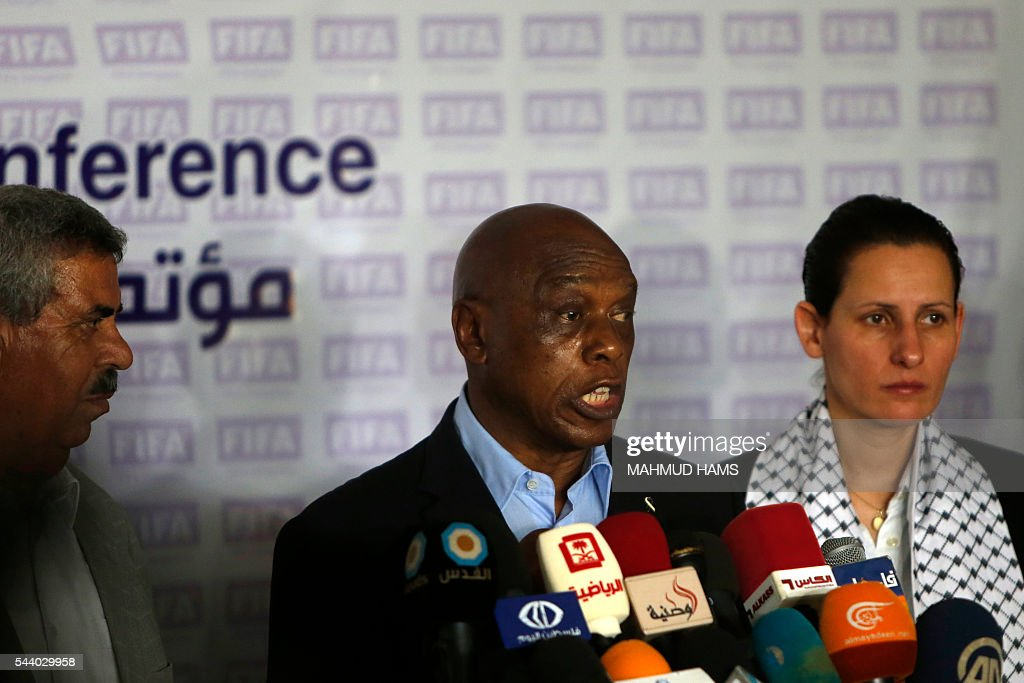 Chairman of the FIFA monitoring committee for Israel and Palestine, Tokyo Sexwale (C), speaks to the press following a visit to the Palestinian Football Association (PFA) headquarters building that was destroyed during the 50-day war between Israel and Hamas-militants in the summer of 2014, in Beit Lahia in the northern Gaza Strip, on July 1, 2016. / AFP / MAHMUD