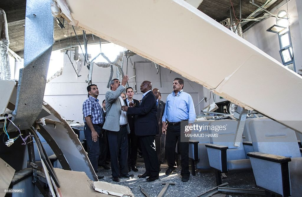 Chairman of the FIFA monitoring committee for Israel and Palestine, Tokyo Sexwale (C), visits the Palestinian Football Association (PFA) headquarters building that was destroyed during the 50-day war between Israel and Hamas-militants in the summer of 2014, in Beit Lahia in the northern Gaza Strip, on July 1, 2016. / AFP / MAHMUD