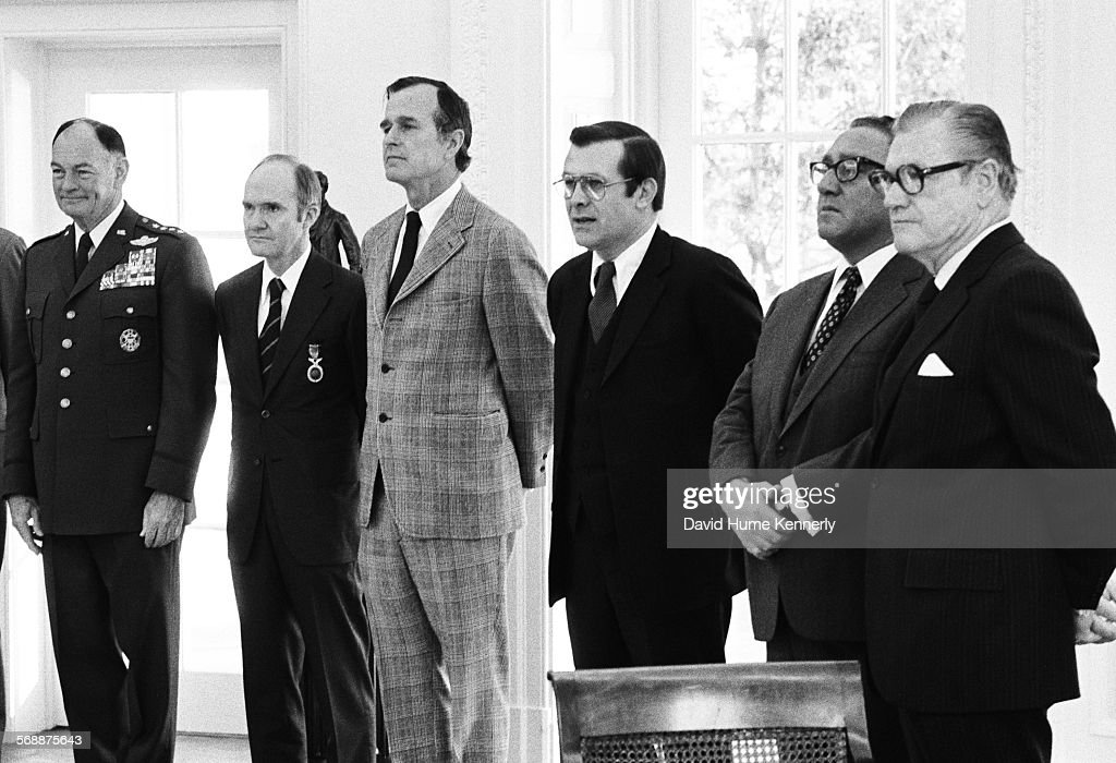 Chairman of the Joint Chiefs of Staff Gen. George Brown, National Security Advisor Brent Scowcroft, CIA Director George Bush, Secretary of Defense Don Rumsfeld, Secretary of State Henry Kissinger, and Vice President Nelson Rockefeller in the Oval Office attending a ceremony honoring Vernon Walters, Washington, D.C., January 19, 1977.