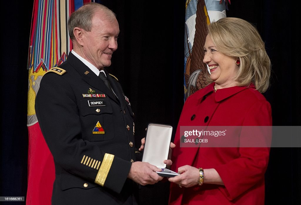 Chairman of the Joint Chiefs of Staff Martin Dempsey presents former Secretary of State Hillary Clinton with the Chairman of the Joint Chiefs of Staff Joint Distinguished Civilian Service Award during a ceremony at the Pentagon in Washington, DC, February 14, 2013. AFP PHOTO / Saul LOEB