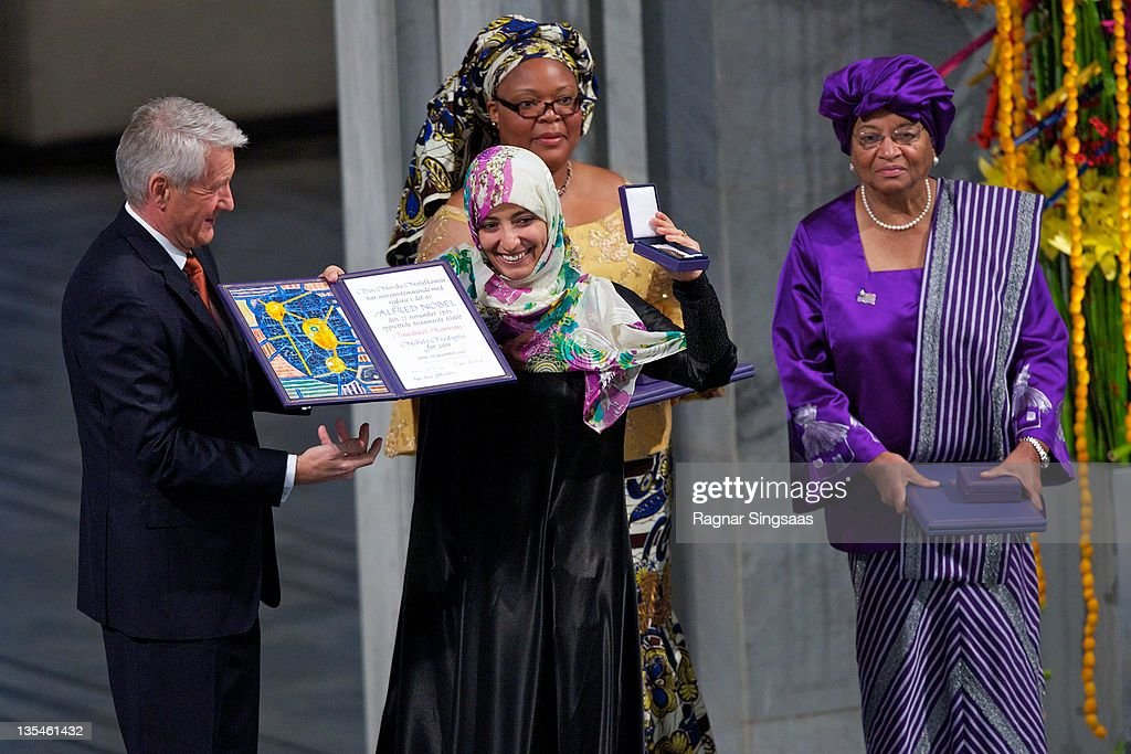 Chairman of the Nobel Committee Thorbjoern Jagland (L), joint winner Liberian activist <a gi-track='captionPersonalityLinkClicked' href=/galleries/search?phrase=Leymah+Gbowee&family=editorial&specificpeople=5133871 ng-click='$event.stopPropagation()'>Leymah Gbowee</a> and joint winner Liberian President <a gi-track='captionPersonalityLinkClicked' href=/galleries/search?phrase=Ellen+Johnson+Sirleaf&family=editorial&specificpeople=547358 ng-click='$event.stopPropagation()'>Ellen Johnson Sirleaf</a> (R) watch joint winner Yemeni journalist and activist Tawakul Karman hold up her award during the Nobel Peace Prize Award Ceremony at Oslo City Hall on December 10, 2011 in Oslo, Norway.